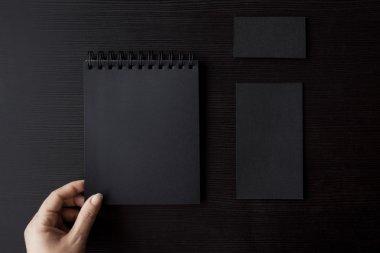 Set of black mockups on dark background,  female hand holding a business card