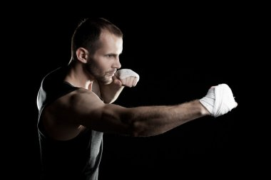 muscular man,strikes right, black background, horizontally