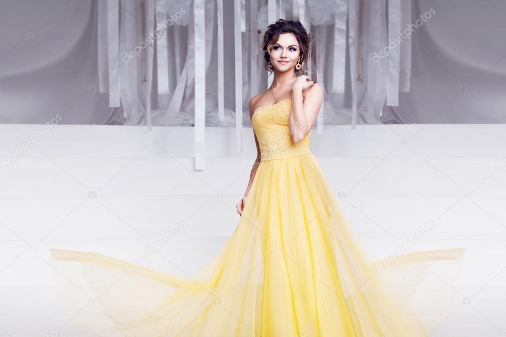 Lächelnde Frau in gelb Abendkleid und mit schöne Frisur, Partei ...