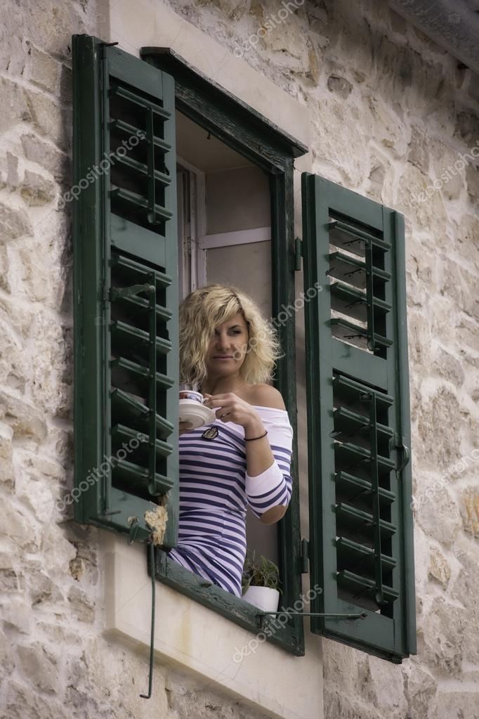 Schone Frau Ist Auf Der Fensterbank Sitzen Und Blickte Stockfoto