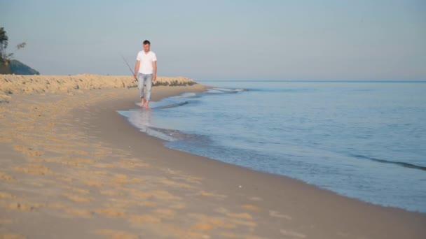 Muž s prutem na pláži