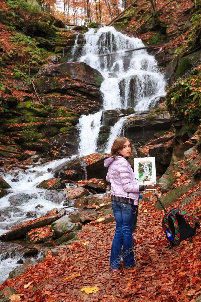 Young painter at work near waterfall