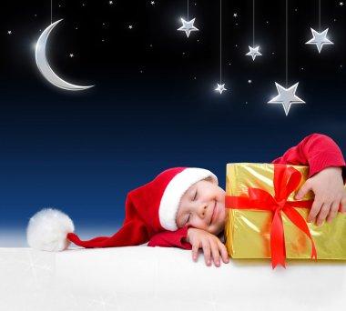 Christmas child is sleeping with gift