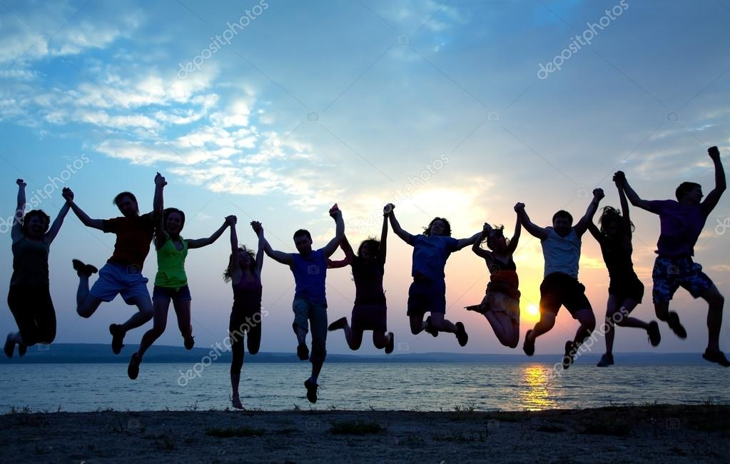Group of  people jumping on beach