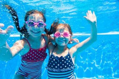 Two little girls underwater in pool