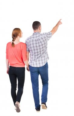 Back view of walking young couple (man and woman) pointing.
