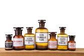 Various vintage pharmacy bottles on wooden board