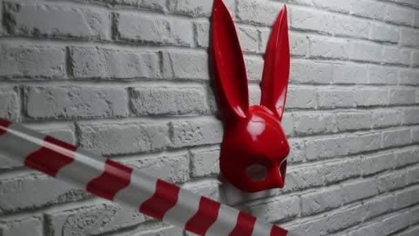 rote Kaninchenmaske auf einer weißen Ziegelwand und rot-weißes Signalband