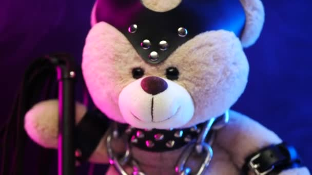 a toy bear wearing leather belts a BDSM accessory is chained with a lock in neon light