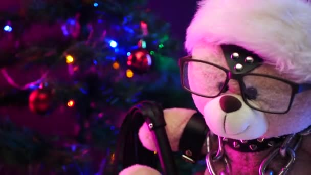 a toy Teddy bear dressed in leather belts and a Santa Claus hat in the New year of Christmas is chained and handcuffed an accessory for BDSM games on a light background of a brick wall texture
