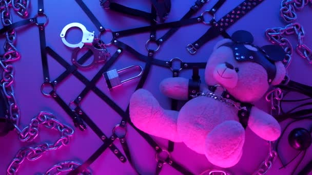 toy bear dressed in leather belt harness accessory for BDSM games on a dark background in neon light in the smoke