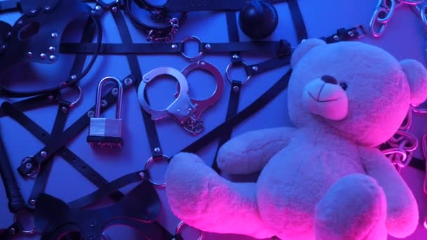 Spielzeugbär in Ledergürtel-Accessoire für BDSM-Spiele auf dunklem Hintergrund in Neonlicht im Rauch