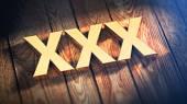 Fotografie Wort xxx auf Holzdielen