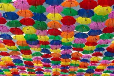 Lots of umbrellas coloring the sky