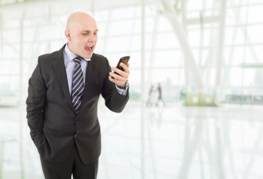 Angry businessman yelling into a cellphone, at the office