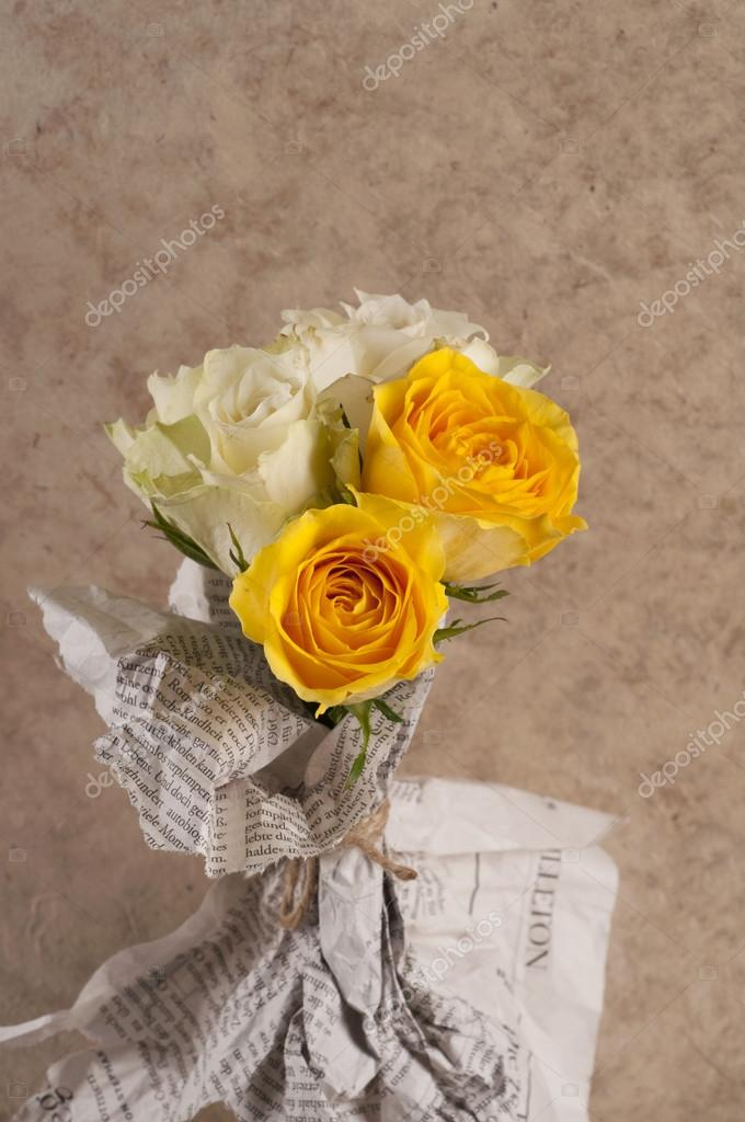Bunch Of Multicolor Rose Flowers Wrapped In Newspaper Over Brown