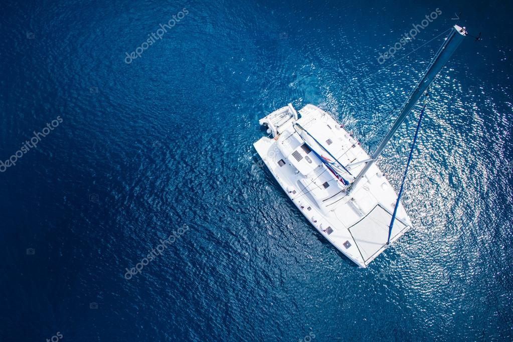 Amazing view to Catamaran sailing in open sea at windy day. Drone view - birds eye