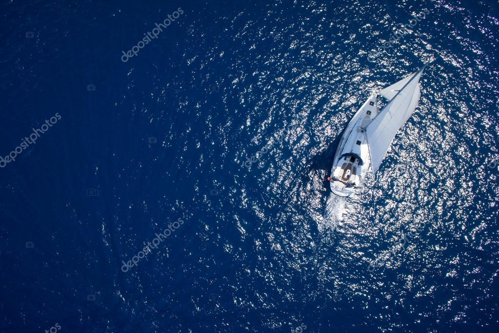 Amazing view to Yacht sailing in open sea at windy day. Drone view - birds eye