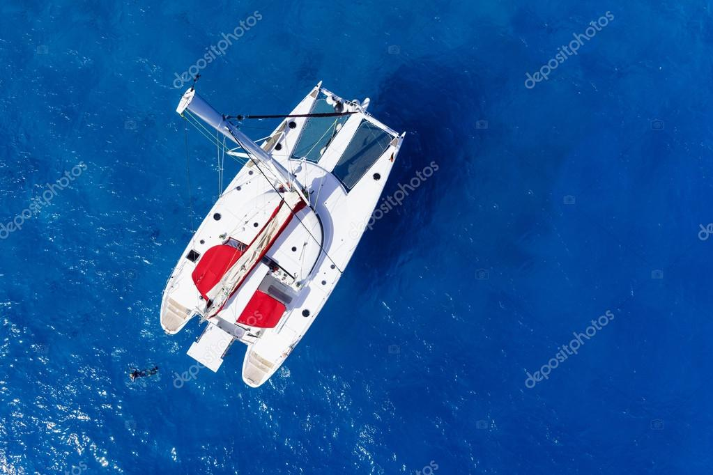 Amazing view to Catamaran cruising in open sea at windy day. Drone birds eye angle