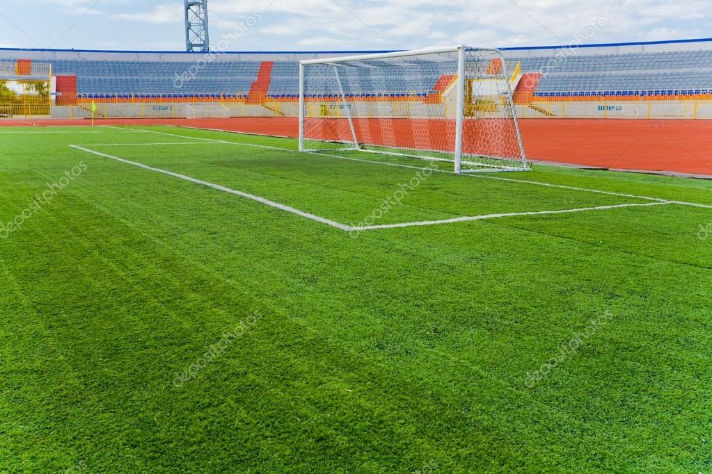 STADIUM - Football field with goal and tablo on blue sky