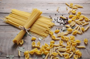 Cooking concept. Uncooked italian pasta: vermicelli, spaghetti with twine on wooden background