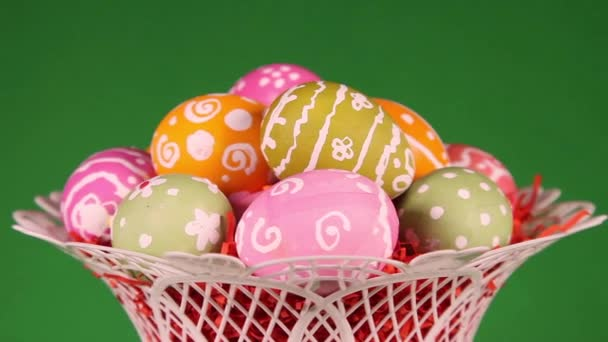 Easter eggs in basket on green