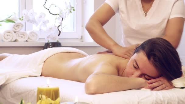 Relaxační žena ležící v posteli v lázeňském salonu, zatímco mladá Asiatka dělá vietnamské masáže s aromatickým olejem