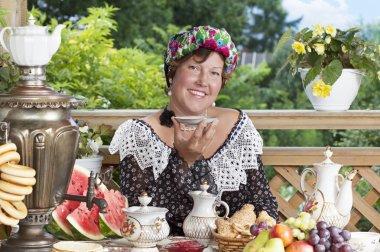 Joyful woman drinking tea outdoors