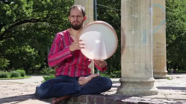 Junger Mann spielt Tamburin im Freien