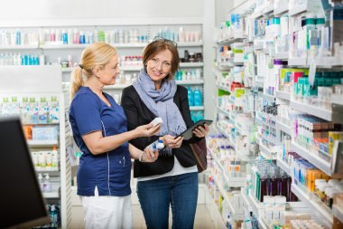 Customer Standing By Pharmacist Showing Medicines In Pharmacy