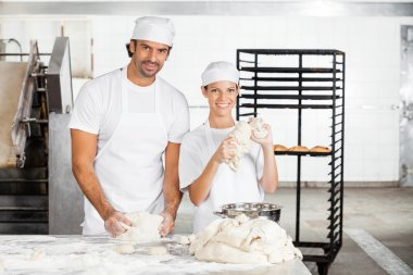 Smiling Bakers Kneading Dough Together In Bakery
