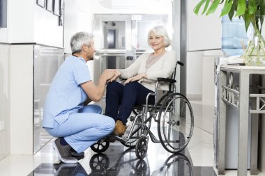 Physiotherapist Holding Smiling Senior Womans Hand On Wheelchai