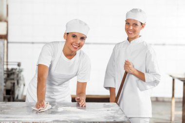 Smiling Female Bakers In Uniform Cleaning Bakery