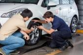 Fotografie Zákazník a mechanik diskutovat nad pneumatika