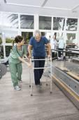 Zdravotní sestra v peelingu pomáhá muž s Walker ve Fitness Studio