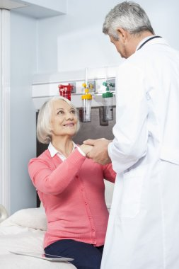 Doctor Holding Patients Hand In Rehab Center
