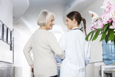 Disabled Senior Patient Standing With Doctor At Rehab Center