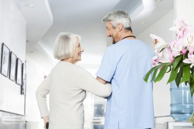 Disabled Senior Woman Looking At Mature Physiotherapist