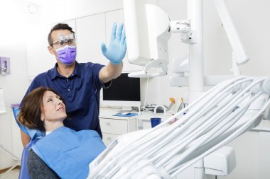 Dentist Explaining Xray To Female Patient In Clinic