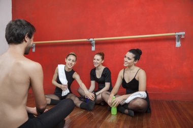 Tired Ballet Dancers Looking At Trainer In Studio