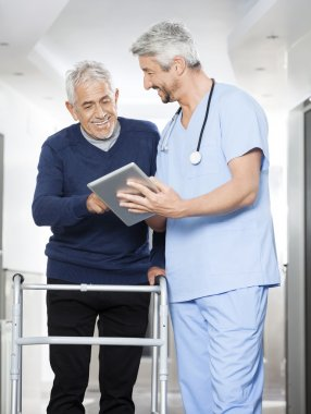 Physiotherapist Showing Reports On Tablet Computer To Senior Man