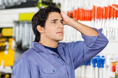 Confused Customer Looking Away In Hardware Shop