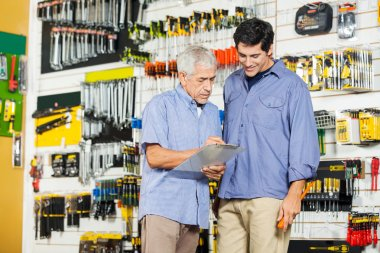 Father And Son Checking Checklist In Hardware Store