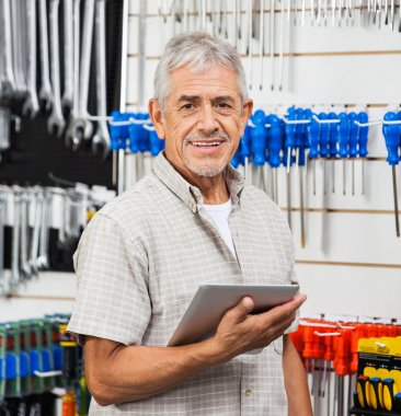 Senior Customer Holding Tablet Computer In Hardware Store