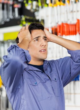 Confused Customer With Hands On Head In Hardware Shop