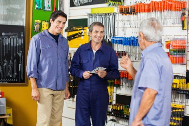 Worker With Customers In Hardware Shop