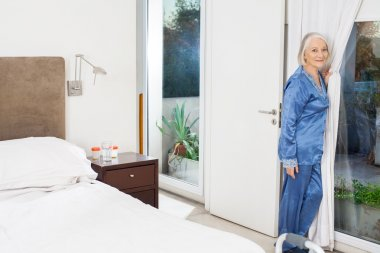 Senior Woman Standing By Window At Nursing Home
