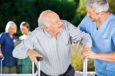 Male And Female Nurses Helping Senior People