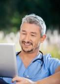 Mužské Domovník, usmíval se při pohledu na tabletový počítač