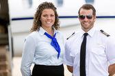 letuška a pilotní stojící proti soukromým letadlem